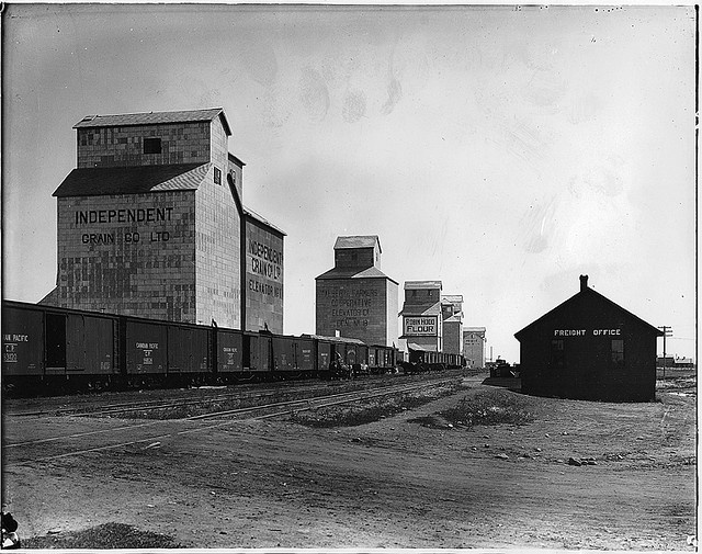 Grain elevators and train, Claresholm, AB, 1918. From the McCord Museum.