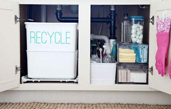under kitchen sink organization: labeled recycle bin, white metal utensil caddy for cleaners, acrylic drawers for rags and sponges (The Container Store), clear container for dish powder {I Heart Organizing}