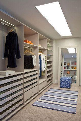 Suíte da Mulher / Apartamento Casal Maduro. No closet da suíte de Pedro Paranaguá, as estantes em laca branca e off white são de Evivva Bertolini. Aqui e no restante do projeto, o piso acarpetado contribui para o conforto.