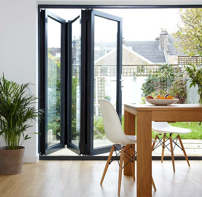 Open Blue Concertina Patio Doors A Table And Chairs Are On The Right