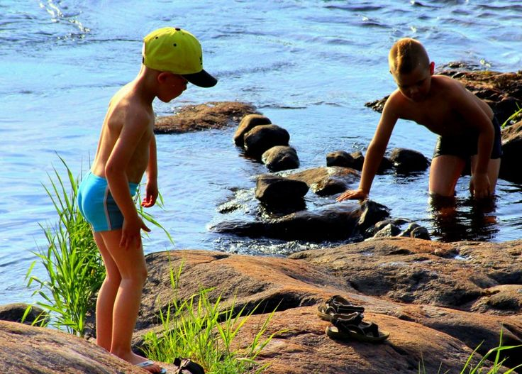 Young swimmers in the Tornionjoki River on a sweltering hot day in July.
