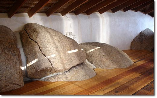 Earthbag walls and natural wooden floor formed around boulders, symbolic of how we should approach building: adapting ourselves to suit the natural, not changing nature to suit us.