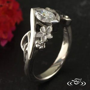 Custom 950 Palladium wrap style mounting holding a marquise cut center diamond with cherry blossoms and pierced leaves on either side of stone.
