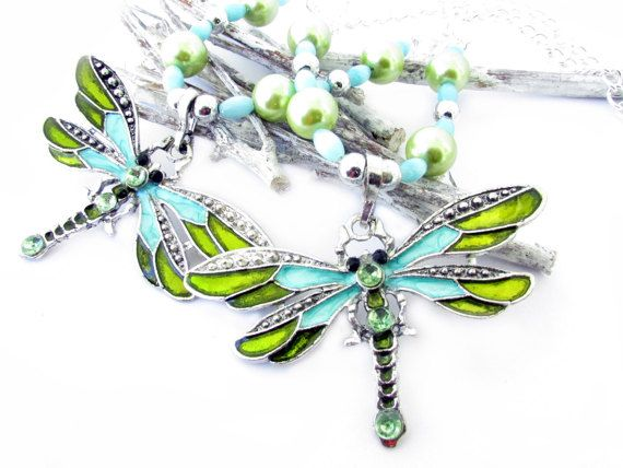 These are absolutely GORGEOUS dragonfly curtain tiebacks made with a silver metal with blue and light green dragonfly bead focal point. There are coordinating blue oval beads and light green pearls with alternating bright silver beads. These curtain tiebacks add sparkle to your room. Perfect drapery tiebacks for the shabby chic decor, or a little girls room.  The large dragonfly pendant measures a full 2.5 inches across by 1.5 long. These are 18 inches long, and this is for 1 set of 2…