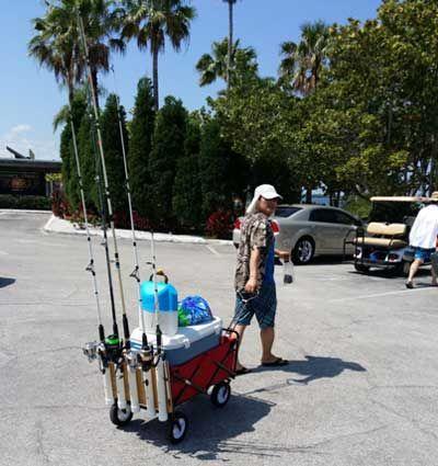 man pulling red collapasible fishing cart