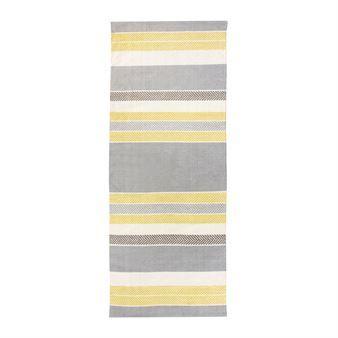 Addera lite färg till din inredning med Marjaniemi matta i gult från Vallila Interior designad av Tanja Orsjoki. Mattan är tillverkad i fin bomull och har ett tidlöst fiskbens- och randmönster i gula toner. Placera mattan i köket eller varför inte i hallen som en fin färgklick