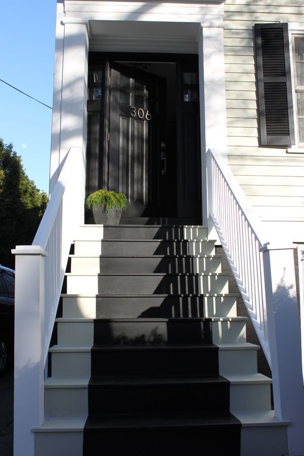 black front door, white house, black painted runner on stairs - love this idea for the stairs
