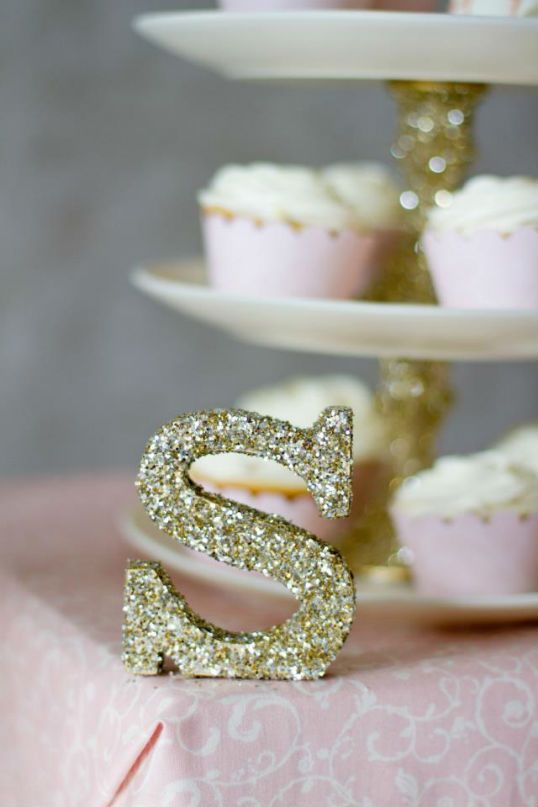 spray painted letters and stands for birthday food with gold glitter