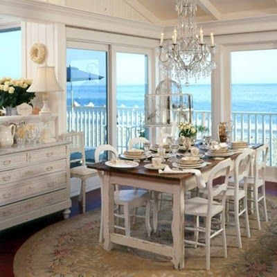 Lovely dining room, formality of a chandelier, oriental rug, elegant white, yet looks casual.  Every room in a beach cottage should have this view.