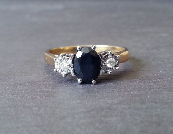 {Blue Sapphire & Diamond Trilogy Engagement Ring}  An oval sapphire gemstone is the centrepiece of this gold trilogy ring. With two bright diamonds at
