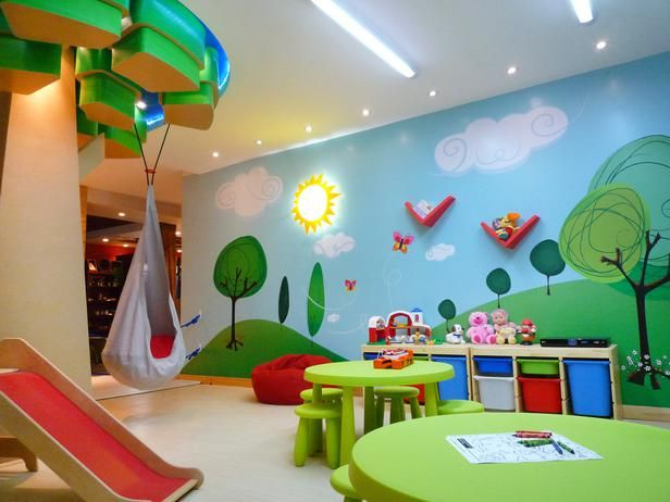 A forest mural is the focal point in this outdoor-inspired kids' playroom. The column in the middle of the room is transformed into a tree featuring a swinging seat for a place for the kids to read a book. Co-architects: Juan Manuel Rodriguez and Jose David Jimenez