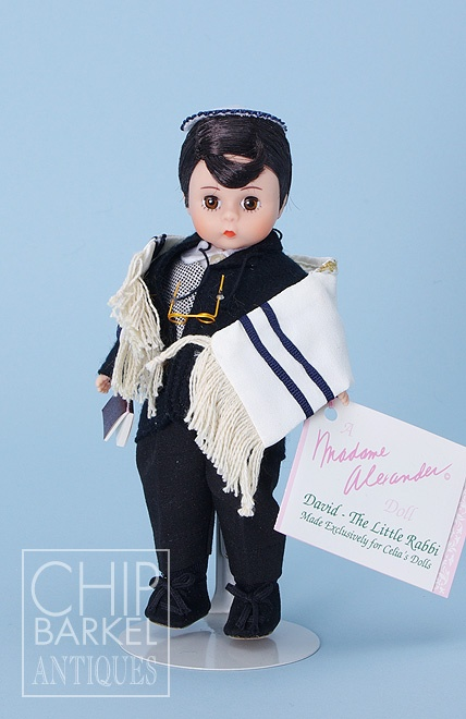 """Name: David The Little Rabbi Made exclusively for Celia's Doll Shop in Florida  Maker: Madame Alexander  Size: 8""""  Medium: Hard Plastic   Date: 1991  Description: Limited to 3,500 dolls. Adorably dressed in traditional rabbinical garb, suit, vest, prayer shawl, yarmulke, glasses, prayer book, and wrist tag.  Marks:   body: Alexander  clothing: Made Exclusively for Celia's Dolls, David The Little Rabbi, Madame Alexander  Condition: Mint in Original Box. NFRB    Price: $50"""