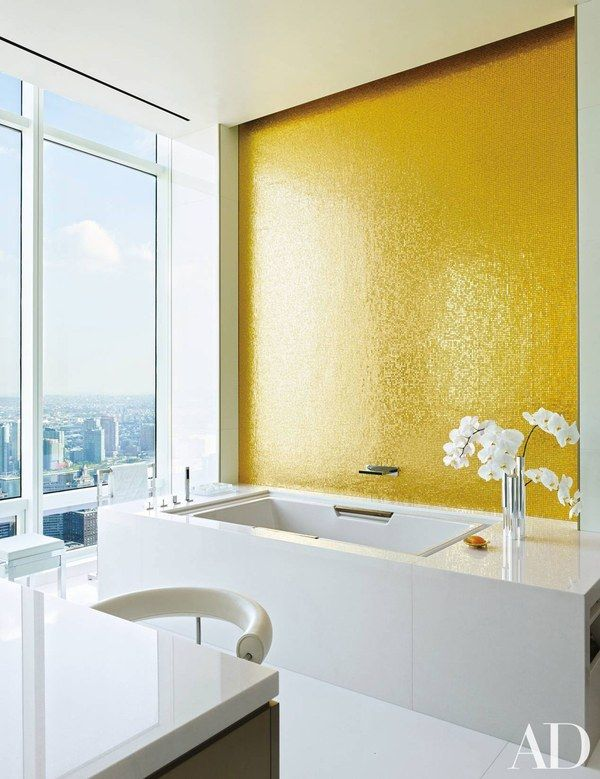 A wall in the bath of a New York penthouse by the Rockwell Group is embellished with gold-leafed glass-mosaic tile | archdigest.com