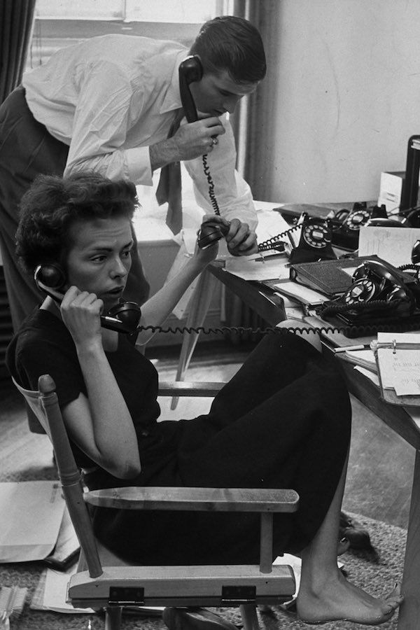 1948 Ford Modeling Agency co-owner Eileen Ford and her husband answering calls requesting one of their 34 high fashion models. They're in her third floor office in New York.