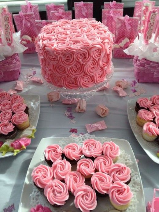 Pretty pink rosette baby shower cake and cupcakes are the focal point for this baby shower table. Pink party favor bags are lined up in the back.