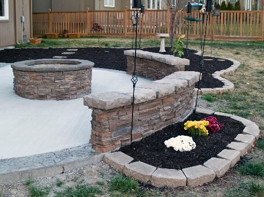 Concrete Patio Covered by Shingled Roof, Stone Veneered Sitting Walls and Wood Burning Fire Pit in Olathe, KS