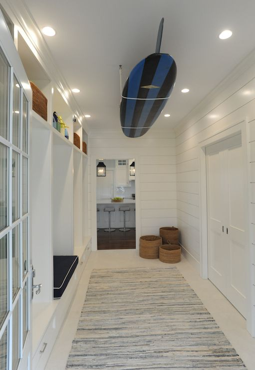 Fabulous beach mud room with wall length, built-in lockers featuring a built-in storage bench with overhead cubbies alongside wood planked walls with a ceiling mount surfboard over ivory floors layered with a gray rag rug.