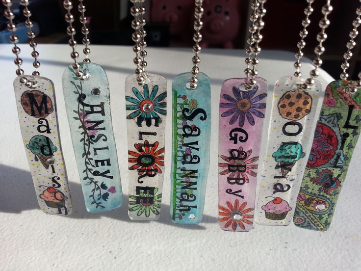 "Name tags created with Shrinky Dinks paper, rubber stamps, coloring pencils/Sharpies. Decorative stamps done on ""frosted"" side and colored. Names stamped on shiny side, so as to give some dimension the name when looking at it from the front.  Once complete, stick-on gemstones were added for detail and the front was sealed with a layer of Mod Podge Dimensional Magic...which helps keep the gemstones on too.  (I also painted a thin layer over the back for a quick seal and to add shine)"