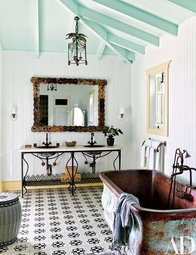 Sconces by Schoolhouse Electric & Supply Co., a mirror by Roost, sink fittings by California Faucets, and handmade floor tile add charm to a guest bath | archdigest.com