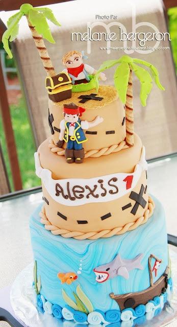 Rose Sucré: Un Gâteau de Pirate    avec palmiers, deux étages. le concept prénom de l'enfant. 1 seul pirate et un petit coffre avec un requin   étage du haut : beige ; étage du bas : bleu