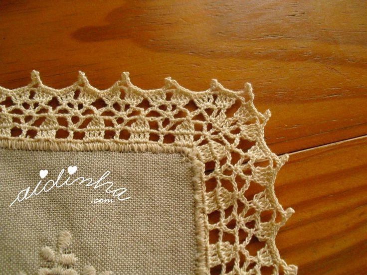 Vista do canto do picô de crochet, da toalha de linho bordada