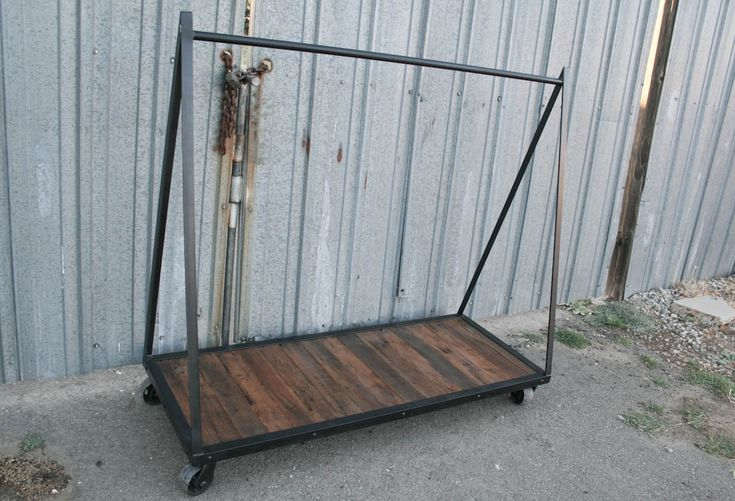 Industrial style clothing rack handmade from steel and reclaimed wood. Unique, customizable rolling garment rack.