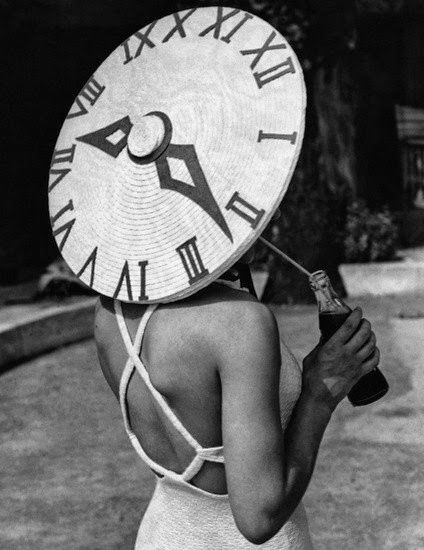 """Dancer Rosemary Andree, wearing her striking """"clock"""" sun hat, takes a drink beside the Roehampton Pool in London. Date: June 1st 1939. Archive: Hulton-Deutsch Collection"""