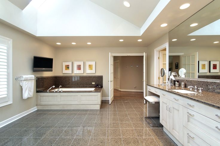 Massive open plan bathroom sports light brown tile, white wood cabinetry on vanity and bath surround, and granite countertop and bath backsplash. Open, sloped ceiling features skylight for natural lighting.