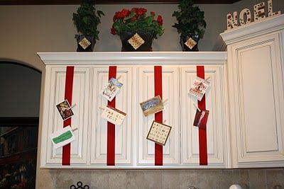Kitchen Cabinet Card Display with wide ribbon tapped inside and clothes pins to pin up cards.