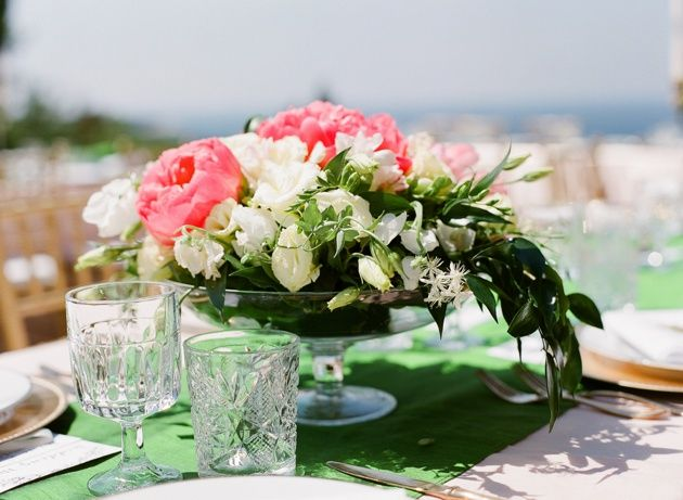 Glass bowl with greenery and pink flowers centrepiece under the Greek sun. Photo by Adrian Wood.