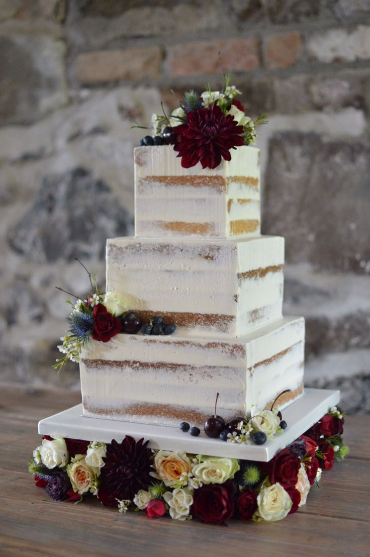 Square semi naked cake on a floral cake stand.