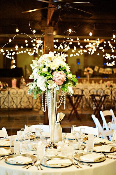 Tall wedding centerpiece designed in a tall silver trumpet vase with hanging jewels.