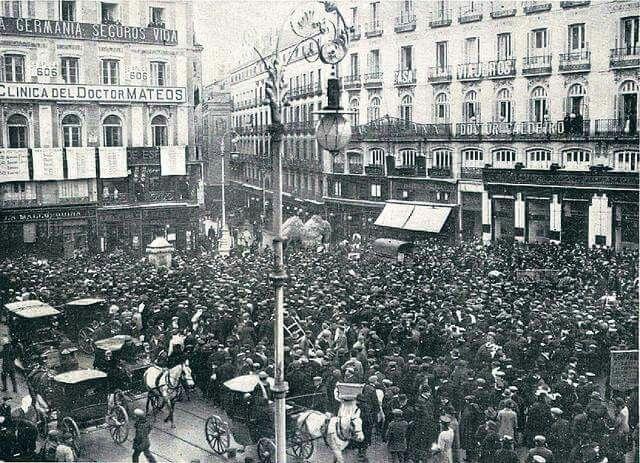 Gente observando las listas con los números premiados del sorteo de la lotería de Navidad, en los balcones del periódico La Correspondencia de España en la Puerta del Sol, el 22-12-1910.