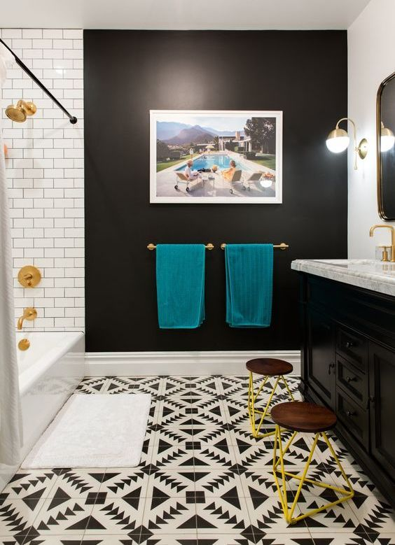 Black and white bathroom with mosaic floor and teal-yellow decor.