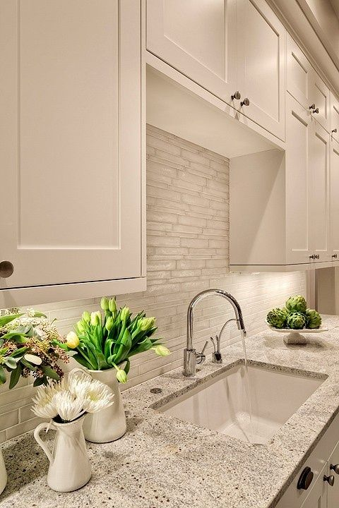 Lovely creamy white kitchen design with shaker kitchen cabinets painted Benjamin Moore White Dove, Kashmir White Granite counter tops, polished nickel modern faucet and Vetro Neutra Listello Sfalsato Glass Mosaic- Bianco tiles backsplash. Benjamin Moore White Dove.: