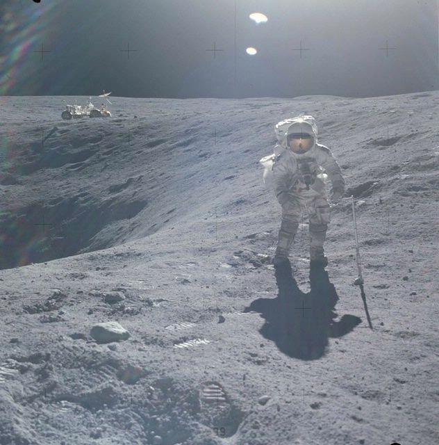 Apollo 16 Astronaut Charlie Duke at edge of crater.