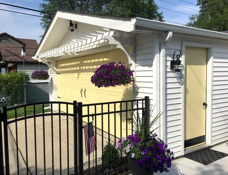 "Garage pergola over Benjamin Moore ""Hawthorne yellow behind a Black aluminum fence."
