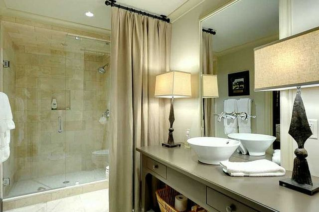 Curtain concealing toilet. Lamps on the counter instead of sconces. Design by Betty Burgess.: