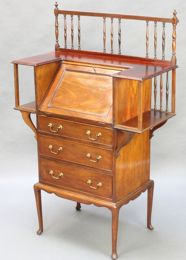"""Lot 961, An Art Nouveau mahogany bureau with railed back, the fall front flanked by a pair of recesses the fall front with well fitted interior with pen recess and 2 ink wells above 3 drawers, raised on cabriole supports 52""""h x 33""""w x 16""""d est £75-120"""