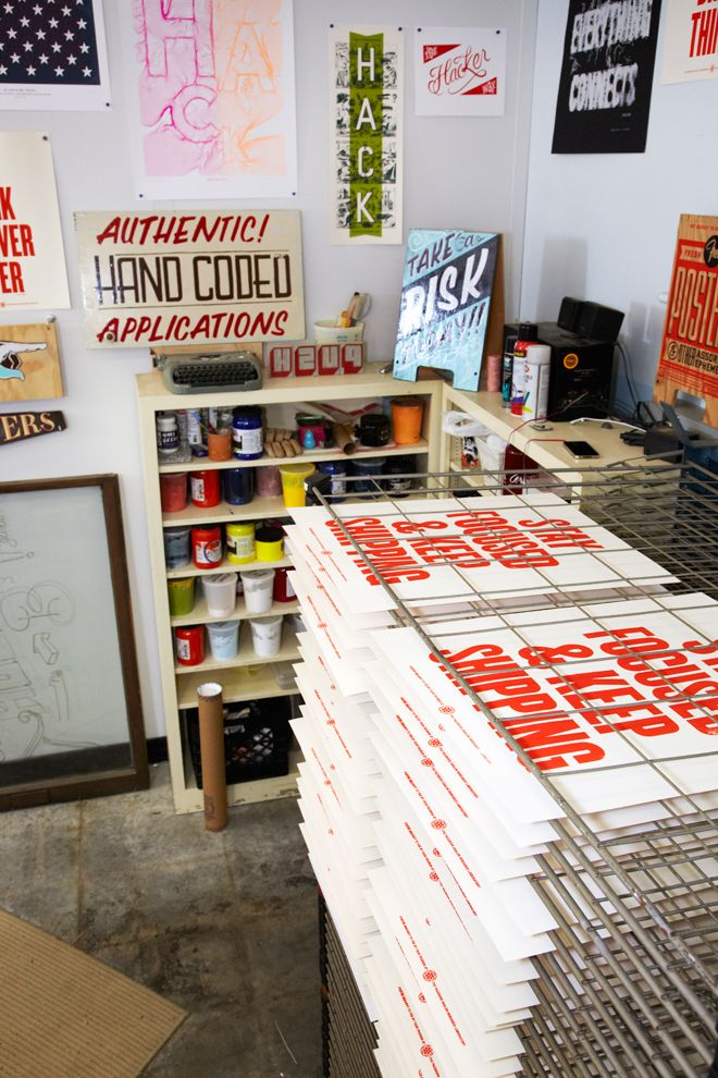 Posters drying on metal racks at Facebook's Secret Propaganda Arm: The Analog Research Lab