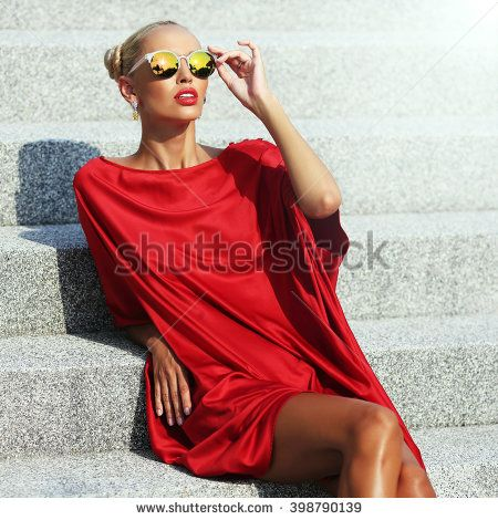 Fashion portrait of elegant stylish girl in a red dress and sunglasses