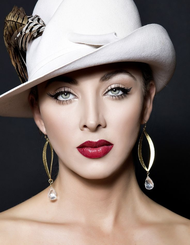 Women's updo hairstyle wearing a white fedora hat with feathers