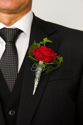 Red Rose Boutonnieres A red rose and some ivy leaves make this an elegant boutonniere. Complements the groom very well.