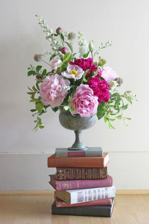 Floral Arrangement of Pink Peonies In Concrete Urn On a Stack of Vintage Books #graduatino #flowers