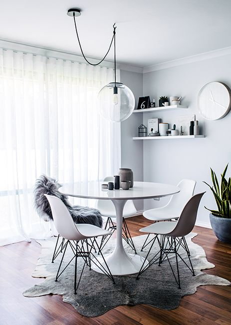 modern white and grey dining room area with round white table and white chairs
