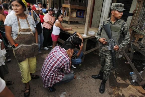 Onlookers stand by as friends mourn for a young man who was shot amidst what local media claimed are accusations of extortion from vendors at a market in Tegucigalpa, Honduras August 26, 2014. Honduras is blighted with the world's highest murder rate, at 90.4 homicides per 100,000 people, according to the United Nations. REUTERS/Jorge Cabrera