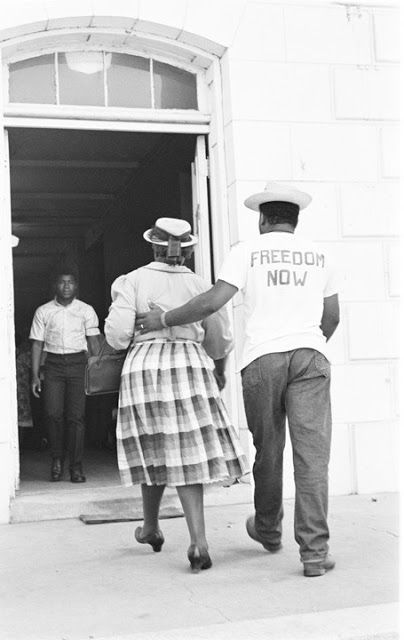 MISSISSIPPI 1964 | Photo: CORE worker accompanying a woman to the courthouse, where she will try to register to vote.  In 1964, 45% of Mississippi's population was Black, but less than 5% of Blacks were registered to vote state-wide.   Registering voters in Batesville, Mississippi during Freedom Summer, 1964. Civil rights workers survived more than 400 acts of violence during the 10 weeks of Freedom Summer.  (photo by Robert Brand)