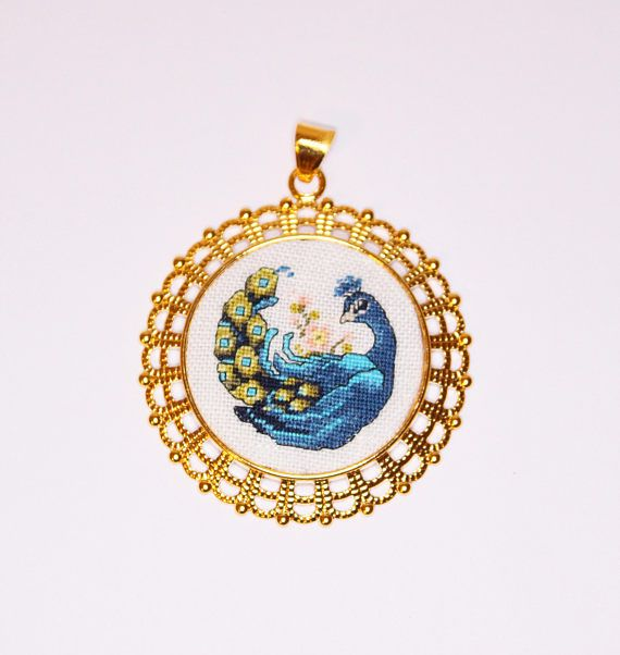 An elegant and slightly shy peacock is hand-embroidered in the petit point technique (256 stitches in square centimeter). Pendant big but not heavy. Bright and shiny - it will undoubtedly draw attention to his owner. Ideal complement your image and will be a wonderful gift for the stylish lady. Treat yourself or give a unique gift to someone! Embroidery is made on white linen fabric with cotton floss DMC. We use high-quality gold pewter findings. The diameter of the pendant is 5.5 cm (2.2…