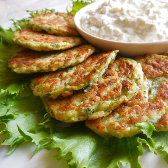 Light, savory zucchini pancakes with a cool tangy yogurt dressing. A healthy Mediterranean snack.