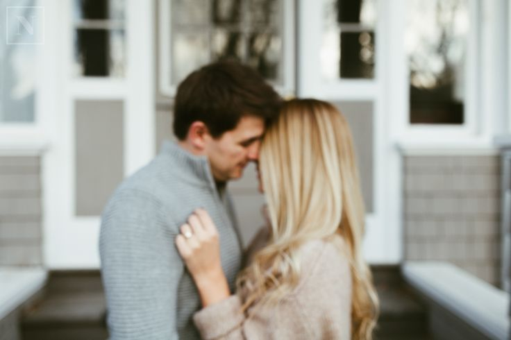 a blurred image of a young couple outside of their home